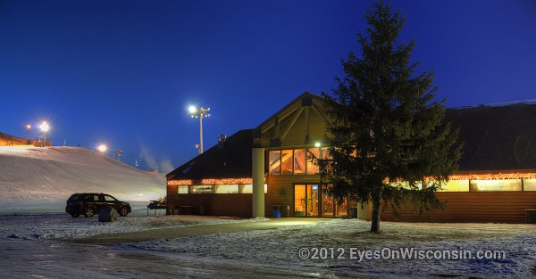 A night photo of Crystal Ridge Ski Lodge with the ski hill in the background