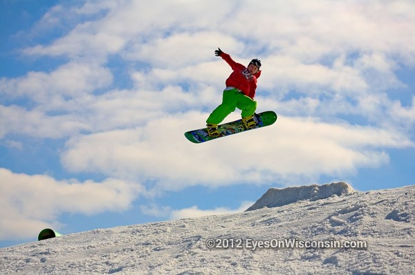 A photo of a snowboarder high off a jump