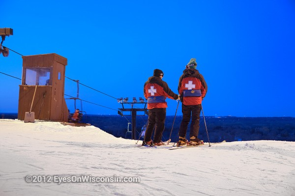 A photo of two members of the ski patrol watching the slopes