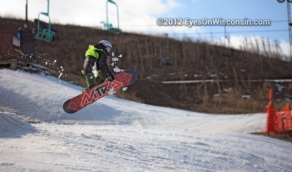 A photo of a snowboarder in the air from a jump